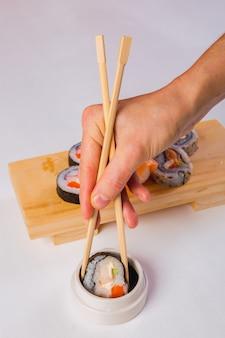 Gros plan des mains tenant des sushis avec des baguettes et trempant dans la sauce soja sur fond blanc.