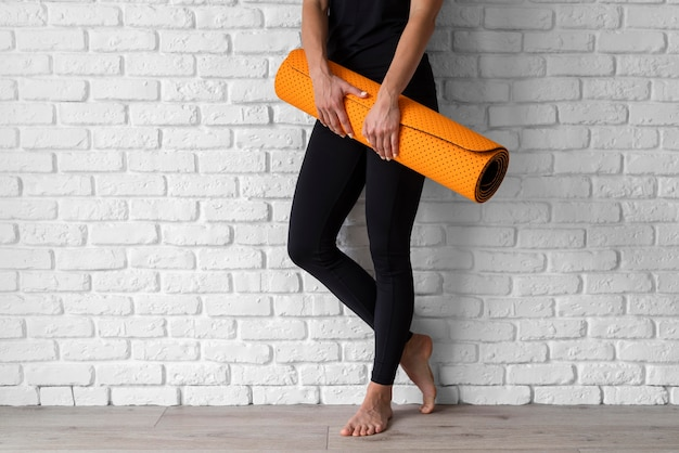 Gros plan mains tenant un tapis de yoga