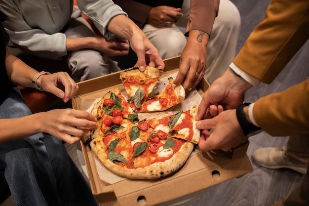 Gros plan des mains tenant des tranches de pizza