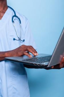 Gros plan des mains tenant et utilisant un ordinateur portable moderne
