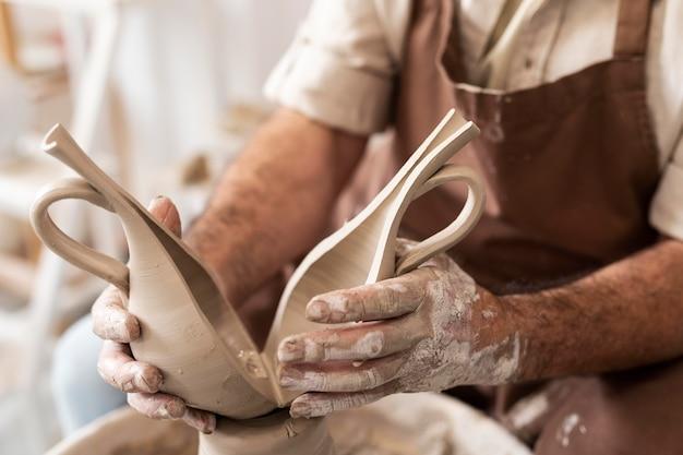 Gros plan des mains tenant un vase