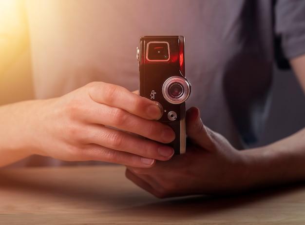 Gros plan sur les mains tenant un vieil appareil photo argentique vintage. objectif photo rétro.