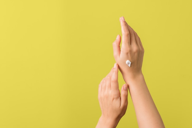 Gros plan des mains tendres d'une jeune femme avec une crème hydratante sur fond jaune. protection de la peau au printemps