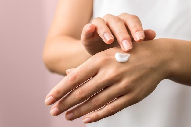 Gros plan des mains tendres d'une jeune femme avec une crème hydratante. protection de la peau au printemps