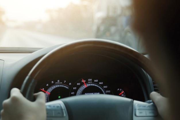 Gros plan des mains tenir le volant jeune homme conduisant une voiture sur la route. voyage de conducteur de voyage.