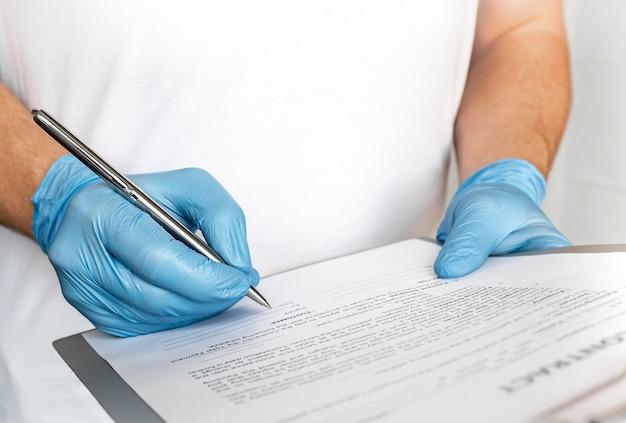 Gros plan des mains de thérapeute homme médical professionnel dans des gants bleus signant un document médical sur le presse-papiers.