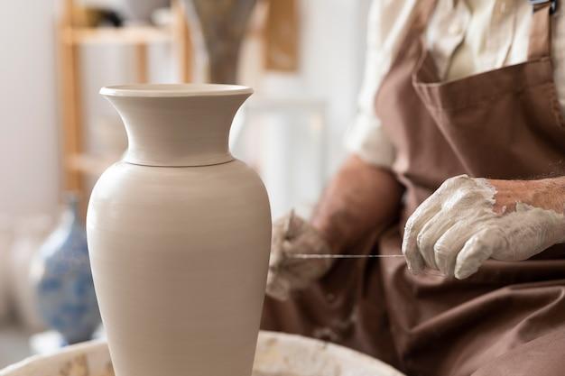 Gros plan sur les mains travaillant avec de l'argile