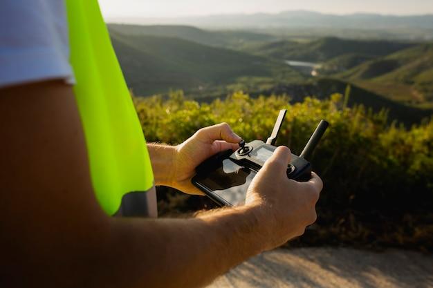 Gros plan des mains de travailleur masculin tenant une télécommande de drone dans la campagne