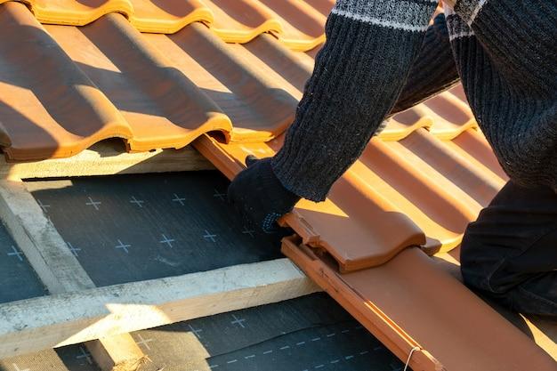 Gros plan des mains des travailleurs installant des tuiles de toiture en céramique jaune montées sur des planches de bois couvrant le toit d'un bâtiment résidentiel en construction.