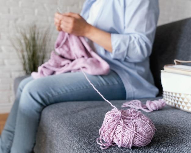 Gros plan des mains à tricoter sur le canapé