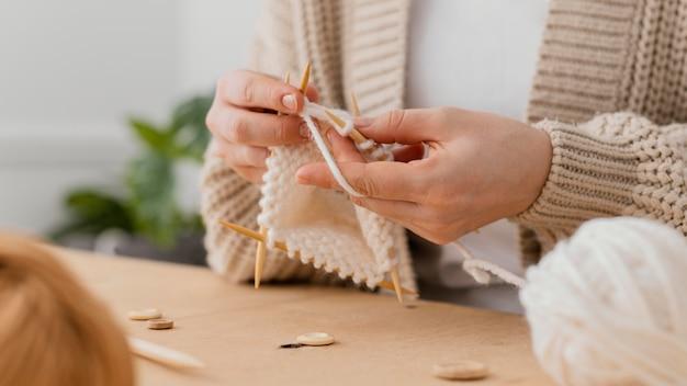 Gros plan des mains à tricoter avec du fil blanc