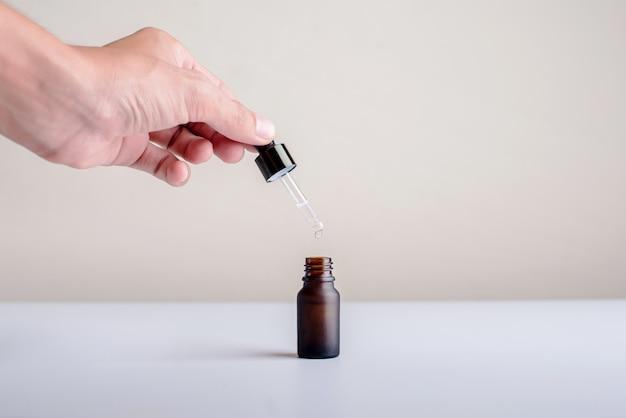 Gros plan des mains utilisées sérum tombant sur sa bouteille