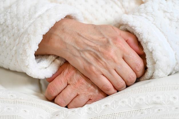 Gros plan des mains d'une vieille femme repliée l'une sur l'autre. femme âgée aux mains jointes.