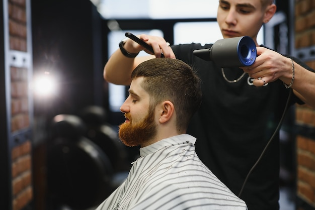 Gros plan, le maître coiffeur fait la coiffure et le style avec des ciseaux et un peigne. concept barbershop.