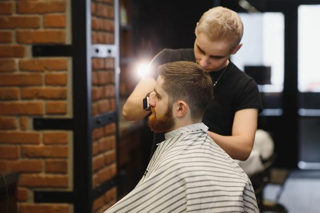 Gros plan, le maître coiffeur fait la coiffure et le style avec des ciseaux et un peigne.