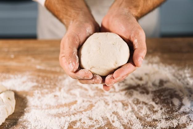 Gros plan, mâle, boulanger, tenue, pétrir, pâte, main, sur, table bois