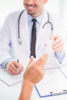 Gros plan, mâle, docteur, donner, pot, de, pilules, à, patient