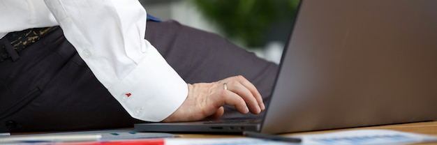 Gros plan, mâle, fonctionnement, affaires, papiers, bureau ordinateur portable moderne sur le bureau. documents avec diagrammes posés sur table. croissance de carrière et concept de réussite