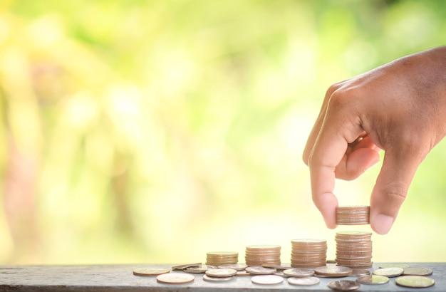 Gros plan, mâle, main, mettre, pièces, pile, pièces économiser de l'argent et financer le concept d'investissement commercial.