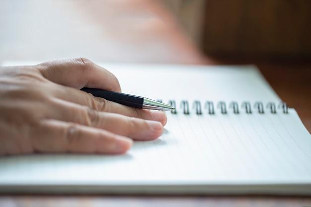 Gros plan, mâle, main, stylo, écrire, cahier, sur, table bois