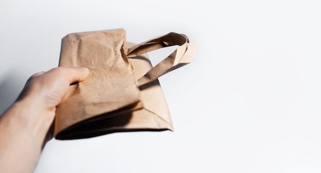 Gros plan, de, mâle, main, tenue, sac papier éco, blanc, surface