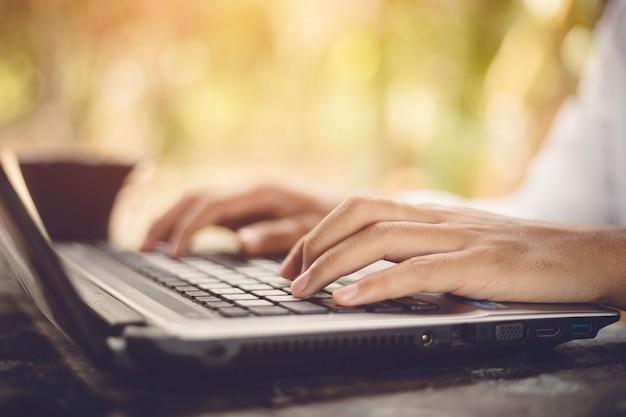 Gros plan, mâle, mains, dactylographie, nature, fond, clavier ordinateur portable