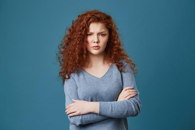 Gros plan de malheureuse jeune femme aux cheveux ondulés rouges et taches de rousseur étant en colère et jaloux de voir son petit ami avec une autre femme.