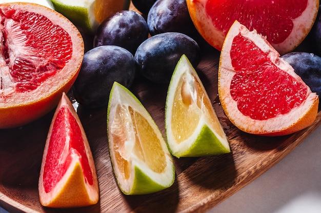 Gros plan d'une mandarine, citron vert, citron, grenade et prunes