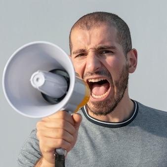 Gros plan d'une manifestante avec un mégaphone criant