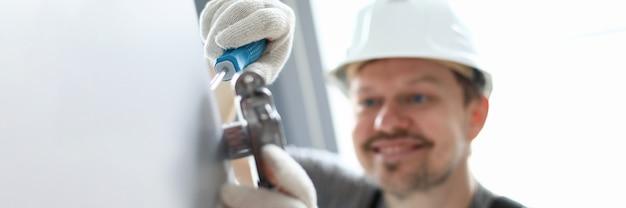 Gros plan, mans, mains, défilement, détail, tournevis, instrument travailleur souriant portant un casque blanc pour le travail. contremaître occupé avec porte. site de construction et concept de bricoleur
