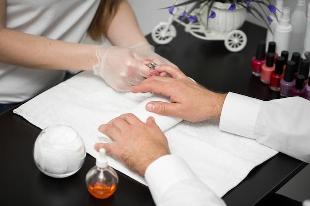Gros plan d'une manucure coupant la cuticule des doigts de la personne