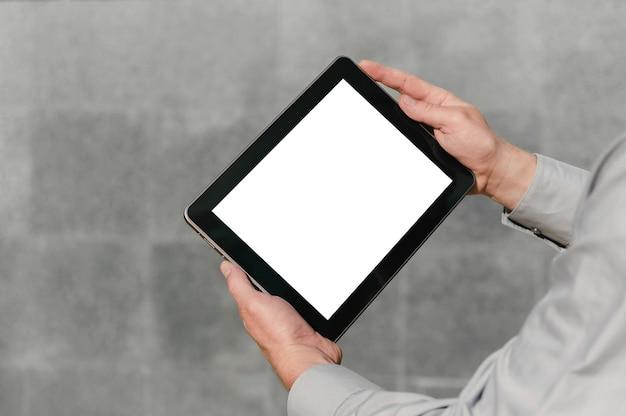 Gros plan, maquette de tablette, dans les mains, d'une personne. sur fond de mur de béton.