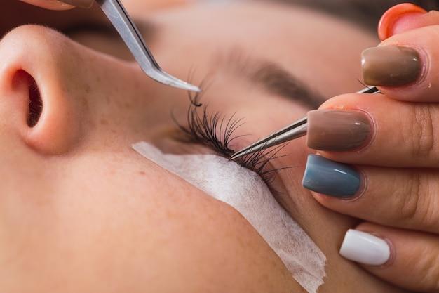 Gros plan d'une maquilleuse travaillant sur les cils d'une femme avec une pince à épiler