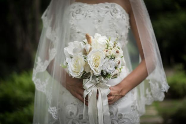 Gros plan de mariée avec fleur de mariée mariage en mains.