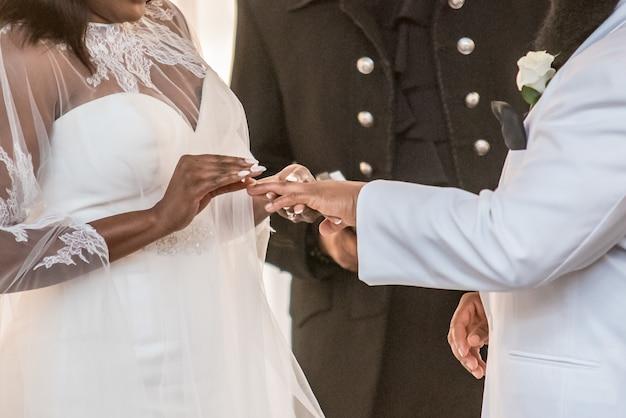 Gros plan de la mariée mettant la bague de mariage sur l'annulaire du marié sur un mariage