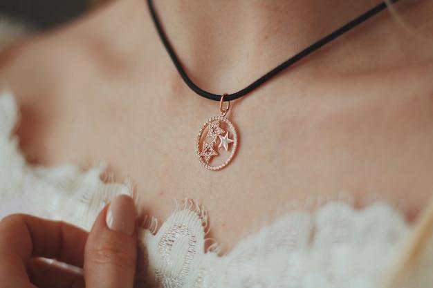 Gros plan d'une mariée portant un collier pendentif avec un cordon noir