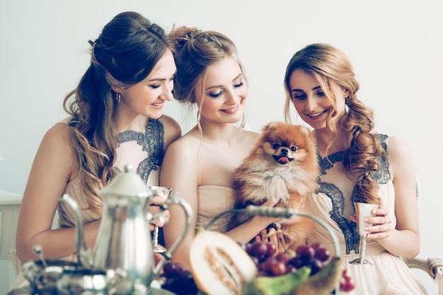 Gros plan sur la mariée avec ses amis et animal de compagnie bien-aimé pendant la partie de bachelorette