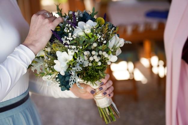 Gros plan de la mariée tenant le bouquet avec de belles fleurs