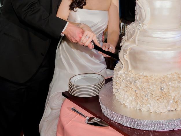 Gros plan des mariés coupant le gâteau de mariage
