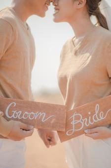 Gros plan des mariés tenant une plaque en bois à l'extérieur. couple romantique et concept de l'amour