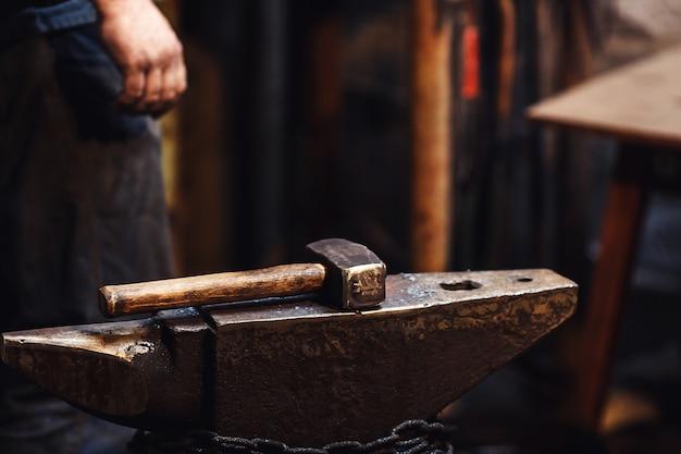 Gros plan d'un marteau de forgeron sur l'enclume.