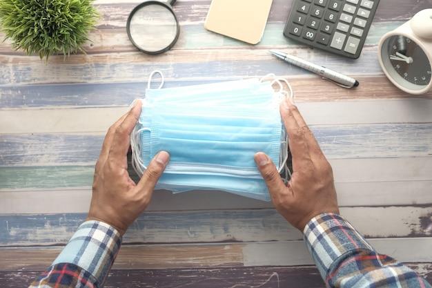 Gros plan de masques chirurgicaux bleus sur le bureau