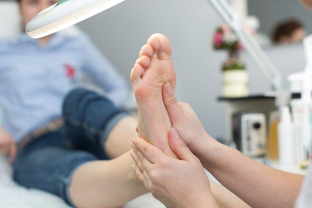 Gros plan d'un massage des pieds au spa