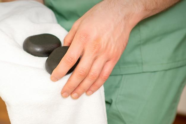 Gros plan des masseurs essuie les pierres de massage noires avec une serviette blanche