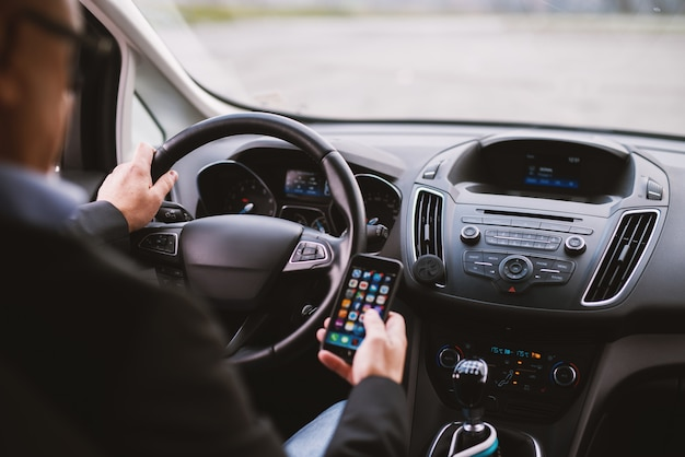 Gros plan mature élégant homme d'affaires élégant professionnel dans un costume conduit une voiture et envoie des sms au téléphone.