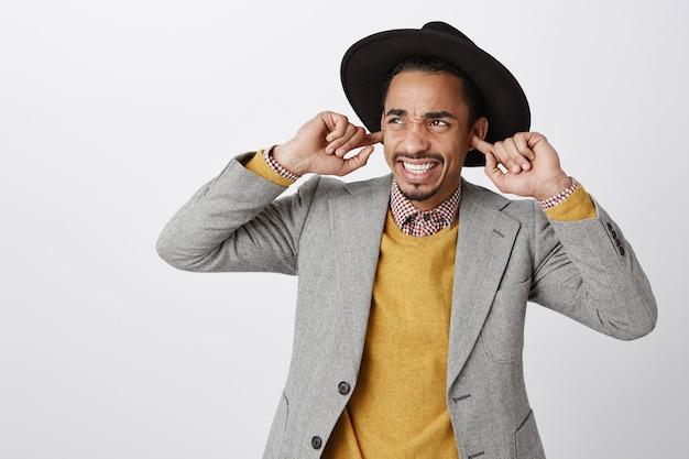 Gros plan d'un mec afro-américain ennuyé et dérangé, ferme les oreilles avec les doigts, ne supporte pas la musique forte et agaçante