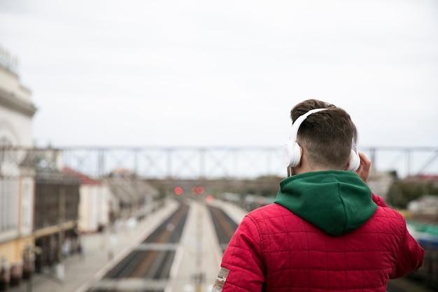 Gros plan mec avec des écouteurs sur un pont