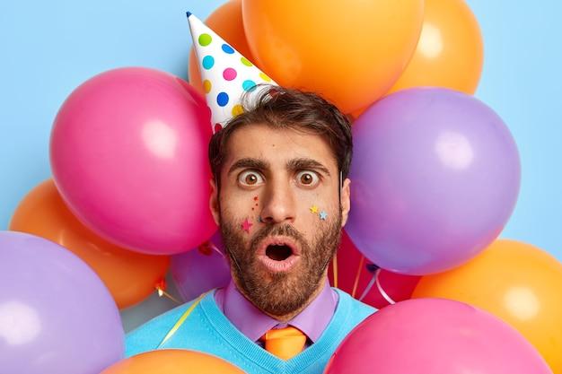 Gros plan d'un mec effrayé entouré de ballons de fête posant