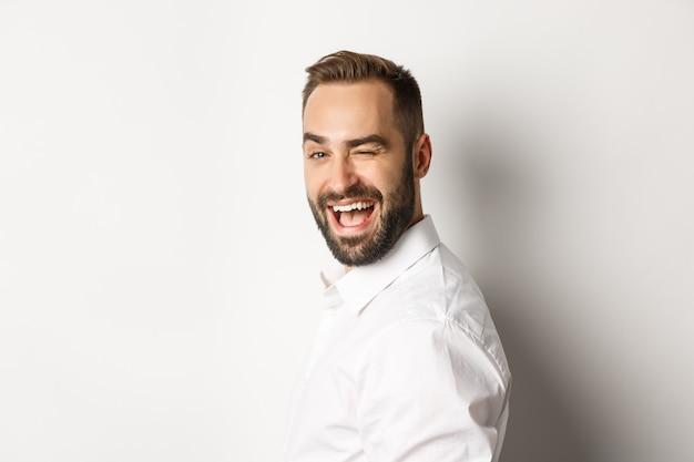 Gros plan d'un mec effronté avec barbe, tourner le visage à la caméra et cligner des yeux avec le sourire, debout