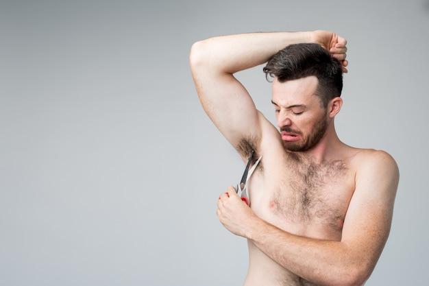 Gros plan d'un mec essayant de couper les cheveux sous son aisselle.